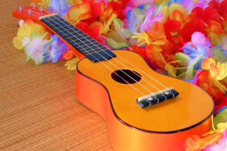 lei: Hawaiian style leis surround a ukelele cast in golden sunlight. Stock Photo