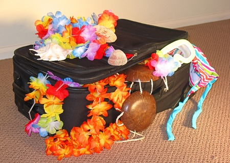 leis: Black suitcase sitting on the floor of a hotel.  Leis, coconut bra, and swimming suit hanging out.