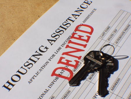 Application for housing assistance stamped Denied in bold red letters. photo