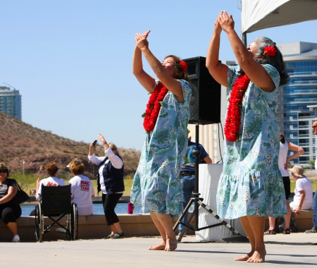 Two women dance to Hawiian music, wearing print dresses and lei, during the Dragon Boat Festival at Tempe Town Lake 2012