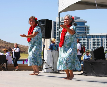 Two women, wearing print dress and lei, dance to Hawiaan music during the Dragon Boat Festival at Tempe Town Lake 2012