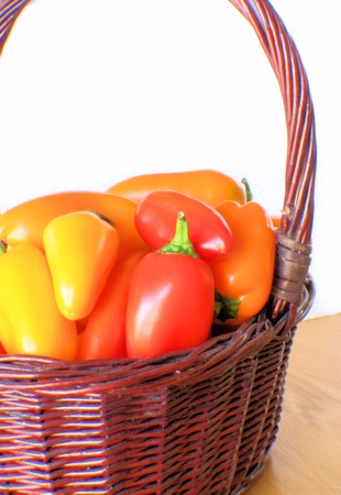 capsicums: Brown wicker basket full of bright colorful peppers.
