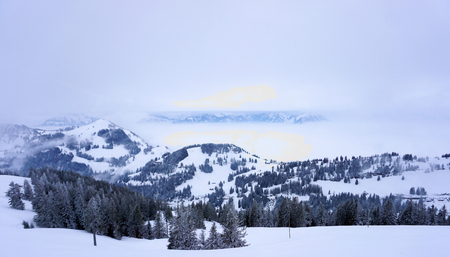 Snow capped mountains peek through clouds on the Alps in Switzerland.
