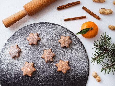 Homemade Christmas shortbread star shape sugar cookies with sugar powder, cinnamon, green fir tree and cookie. Christmas baking. Viewed from above. Vegan Cookies
