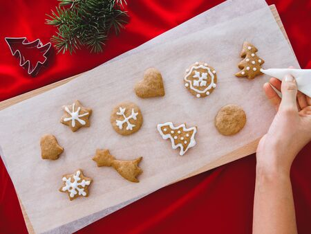 Christmas bakery. Man decorating freshly baked gingerbread cookies with icing and confectionery mastic. Festive food, family culinary, Christmas and New Year traditions concept. Woman decorating honey gingerbread cookies 版權商用圖片 - 137410885