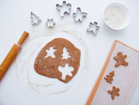Homemade bakery making, gingerbread cookies in form of Christmas tree, gingerbread man. New year treat for Santa Claus cooking. Homemade bakery, xmas sweet, winter holidays concept. Christmas baking background: dough, cookie cutters