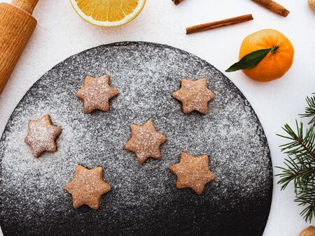 Homemade Christmas shortbread star shape sugar cookies with sugar powder, cinnamon, green fir tree and cookie. Christmas baking. Overhead view. Vegan Cookies. New year treat for Santa Claus cooking. Homemade bakery, xmas sweet, winter holidays concept