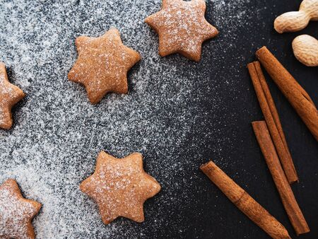 Homemade Christmas shortbread star shape sugar cookies with sugar powder, cinnamon. Food background with christmas spices on a dark slate, stone or concrete background
