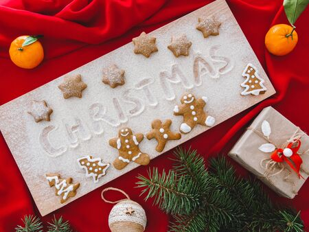 Christmas and New Year background. Composition of gifts, Christmas tree decorations and branches, and gingerbread men on a wooden board, on red cloth. 版權商用圖片