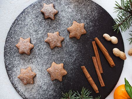 Homemade Christmas shortbread star shape sugar cookies with sugar powder, cinnamon, nuts, green fir tree and cookie. Christmas baking. Overhead view. New year treat for Santa Claus cooking on a black board Homemade bakery, xmas sweet, winter holidays concept.
