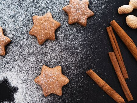 Homemade Christmas shortbread star shape sugar cookies with sugar powder, cinnamon. Food background with christmas spices on a dark slate, stone or concrete background.Top
