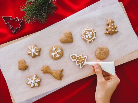 Woman hands holding a culinary bag with meringue cream inprocess of decorating gingerbread man cookies. background concept 版權商用圖片