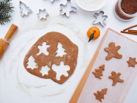 Homemade bakery making, gingerbread cookies in form of Christmas tree, gingerbread man. New year treat for Santa Claus cooking. Homemade bakery, xmas sweet, winter holidays concept. Christmas baking background: dough, cookie cutters tangerines, spice, cocoa, ingredients 版權商用圖片