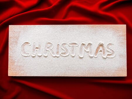 Christmas Inscription on a wooden board Christmas Background, Top View. Concept baner card on red cloth