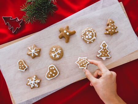 Woman hands holding gingerbread star. Beautiful Christmas background with gingerbread men, Christmas trees and snowflakes, star, with pine, background concept. 版權商用圖片