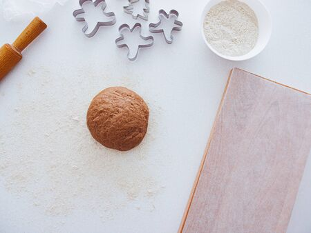Christmas baking background: dough, cookie cutters and spices. Viewed from above. Baking ingredients for Christmas cookies and gingerbread.