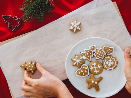 Homemade cookies shaped tree on plate and hand holding Christmas cookies different shapes: star, fir-tree, christmas on white wood background, flat lay.