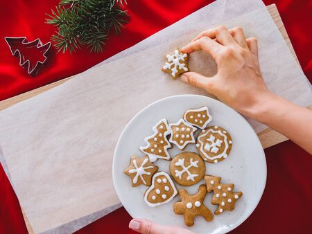 Homemade cookies shaped stars on plate and hand holding.