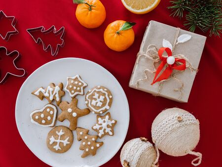 Homemade cookies shaped stars on plate and hand holding. Christmas still life with gift boxes and gingerbread cookies, top view, Christmas background with mandarins. Composition of gifts, Christmas tree decorations and branches, and gingerbread men on a wooden board, on red cloth