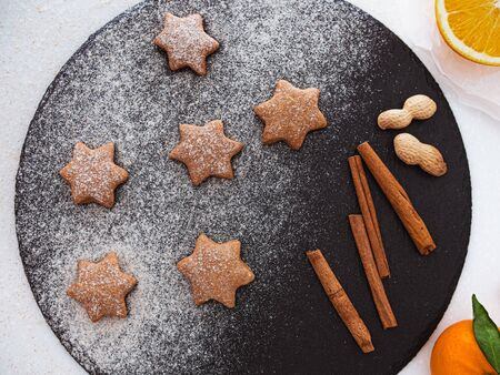 Homemade Christmas shortbread star shape sugar cookies with sugar powder, cinnamon, nuts, and cookie. Christmas baking. Overhead view. New year treat for Santa Claus cooking on a black board Homemade bakery, xmas sweet, winter holidays concept 版權商用圖片