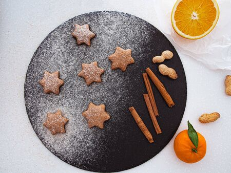 traditional christmas homemade gingerbread cookies, spices and cutting board on dark blue background. holiday, celebration and cooking concept. new year and christmas postcard. flat lay, top view.