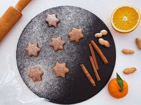 traditional christmas homemade gingerbread cookies, spices and cutting board on white background. holiday, celebration and cooking concept. new year and christmas postcard. flat lay, top view. 版權商用圖片