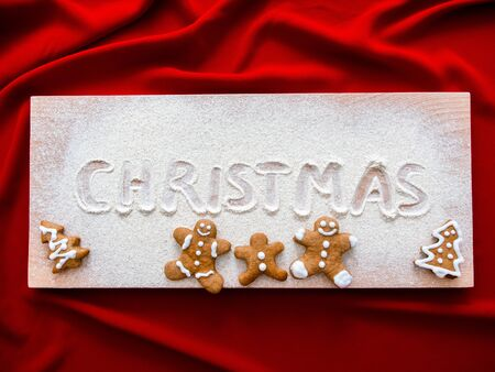 Merry Christmas Inscription on Christmas Baking-Cooking Background, Homemade gingerbread couples on wooden table. beautiful Christmas background with gingerbread men, trees