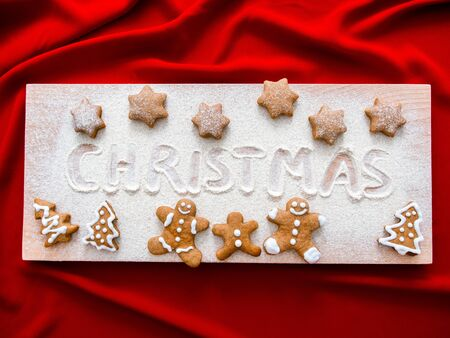 Homemade gingerbread couples on wooden table. beautiful Christmas background with gingerbread men, trees and star. Merry Christmas Inscription on Christmas Baking-Cooking Background, Top View. 版權商用圖片