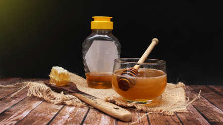 Honey is nutritious for health, stirring with a honey spoon and honeycomb Reklamní fotografie