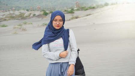 Asian hijab girl is playing swing in the desert, Gumuk Pasir, Yogyakarta Stockfoto