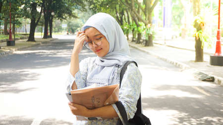 Asian hijab girl reading in the campus garden