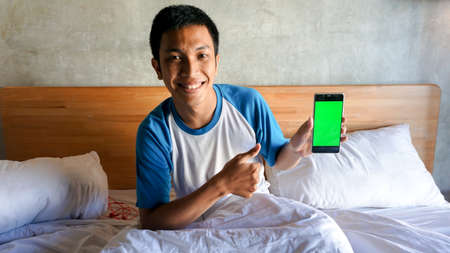Asian man is holding a green screen handphone in the bedroom Stock fotó