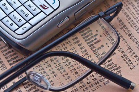 News paper with stock market results, glasses and a cell phone