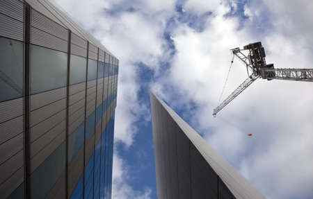 erecting: Construction site with crane over a blue and cloudy sky