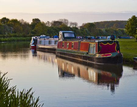 Une rang�e de bateaux sur un canal canal britannique refl�te dans l'eau.