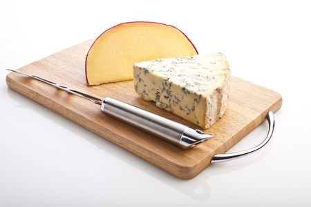 Segments of Brie and Stilton  with a knife on a board photo