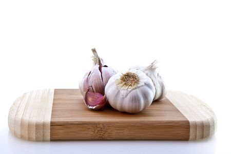 chopping board: Cloves of garlic on wooden chopping board