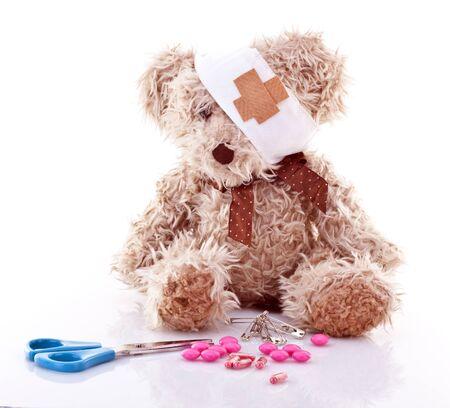 primeramente: Teddy enfermos con los primeros auxilios sobre el fondo blanco Foto de archivo