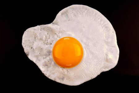 sunny side up: Close up view of the fried egg on black background