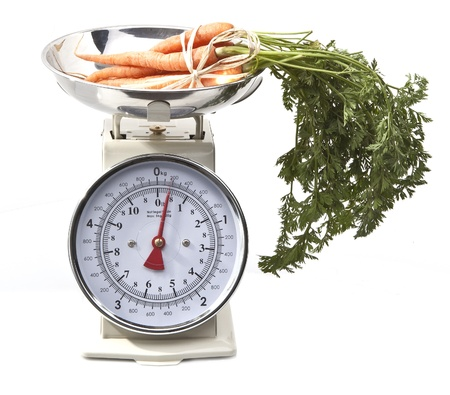 weighing scale: Old style kitchen scales with carrots on white background Isolated Stock Photo