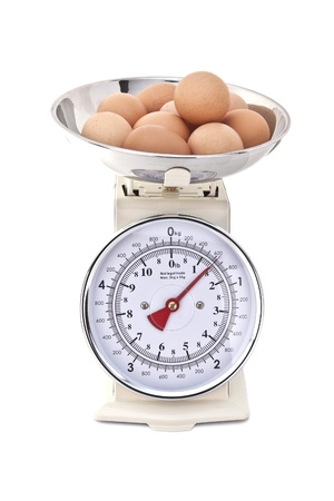 kg: Kitchen Scales with fresh eggs on white background Stock Photo