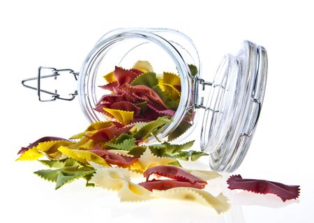 tri color: Colorful dry pasta in a jar on white background  Stock Photo