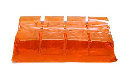 GELATIN: Block of orange jelly cubes on white background