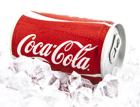 SWINDON, UK - JANUARY 26, 2014: Can of Coca-Cola on a bed of ice over a white background