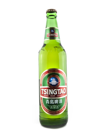 SWINDON, UK - FEBRUARY 2, 2014:  640ml Bottle of Tsingtao Beer on white background, Tsingtao Beer comes from China