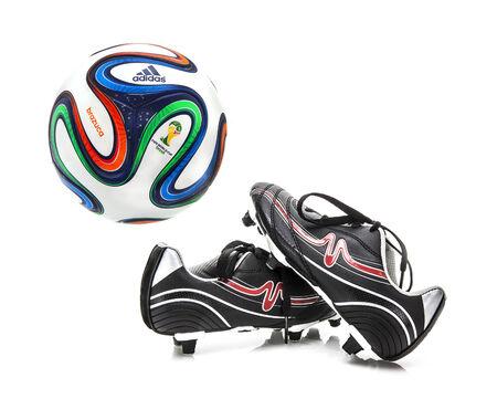 adidas: Swindon, Verenigd Koninkrijk - 8 januari 2014: Adidas Brazuca WK Voetbal van 2014, De officiële Matchball voor het WK 2014 met voetbalschoenen op een witte achtergrond Redactioneel