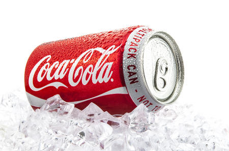 SWINDON, UK - FEBRUARY 2, 2014: Can of Coca-Cola on a bed of ice over a white background