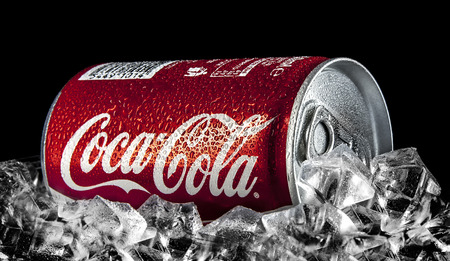 SWINDON, UK - FEBRUARY 2, 2014: Can of Coca-Cola on a bed of ice over a black background