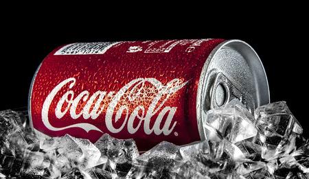 Swindon, UK - 2 februari 2014: Kan van Coca-Cola op een bed van ijs op een zwarte achtergrond