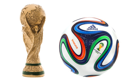 SWINDON, UK - JUNE 11, 2014: FIFA World Cup Trophy and Adidas Brazuca Football on a white Background,  FIFA World Cup Trophy, was introduced in 1974. Made of 18 carat gold with a malachite base Publikacyjne